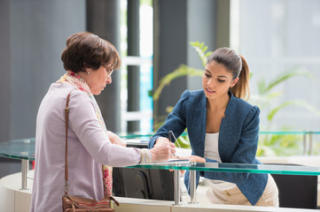 Woman signing paper at reception desk