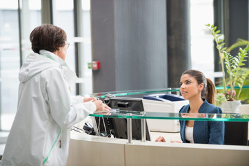 Woman discussing at reception desk