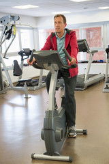 Man exercising on exercise bike in a gym