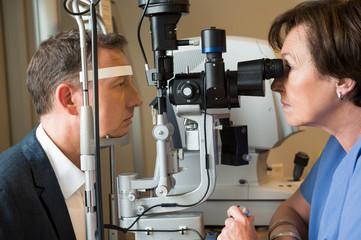 Female optometrist examining man's eyes