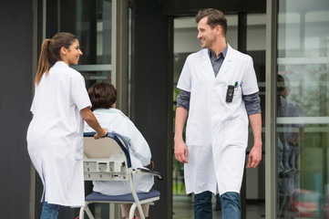 Female doctor pushing a patient on chair while looking at a male doctor