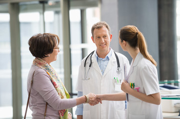 Doctor shaking hands with his patient at hospital reception