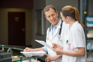 Two doctors discussing at hospital reception desk