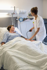 Female nurse checking patient's blood pressure on hospital bed