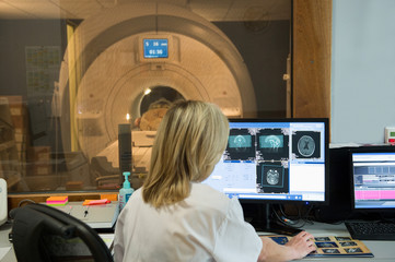 Female doctor examining brain MRI scan on computer