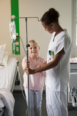 Female nurse assisting to a girl patient in hospital