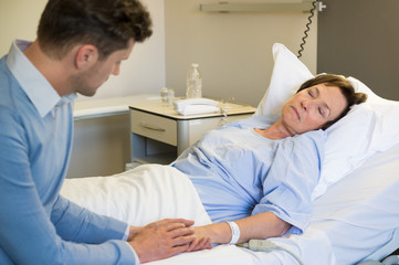 Man holding hands of his mother in hospital bed