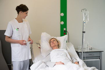 Medical attendant examining a female patient in hospital bed