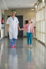 Female doctor walking with a girl in the corridor of a hospital