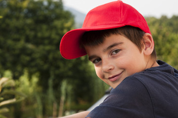 portrait of boy in the foreground with red cap