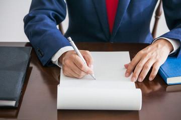 白い紙の上にメモを取るビジネスマン