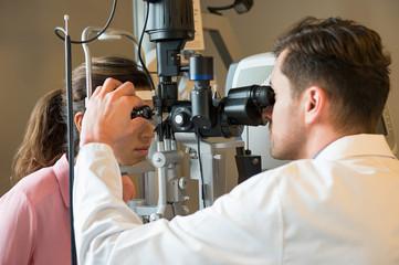 Male optometrist examining woman's eyes