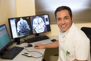 Male doctor examining brain MRI scan on computer