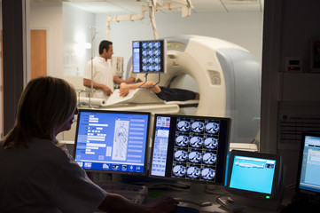 Female doctor examining scan on computer with patient on MRI scanner in background