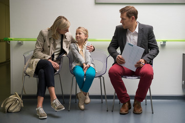 Couple with their daughter sitting in the waiting area of a hospital