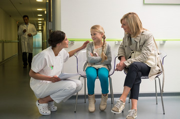 Female nurse talking with patients in waiting room