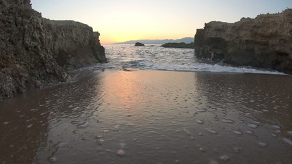 View of waves arriving on sandy beach on sunset