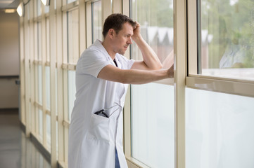 Male doctor standing in hospital looking out of window