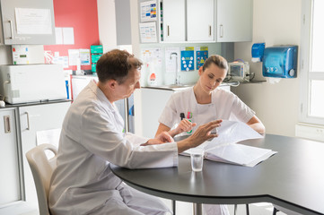 Doctor and nurse analyzing medical record in a hospital