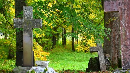 Old stone crosses on graves in autumn