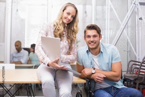 Smiling business people using laptop together looking at camera - 71212586