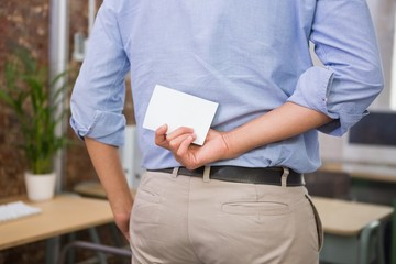 Man holding blank business card behind his back