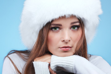 Beautiful girl in a white fur cap and warm clothes on a blue