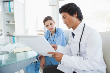 Doctor and surgeon reading notes