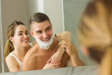 Woman putting shaving foam on boyfriends face