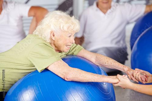 canvas print picture Seniorin macht Fitness in der Reha