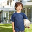 Junge mit Fußball steht im Garten