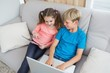 Happy siblings using laptop and tablet pc on sofa