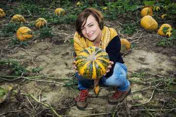Young woman posing with yellow pumpkin in the field