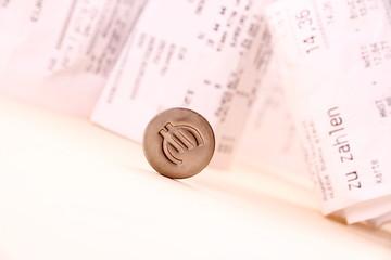 Euro symbol rolled down bills in background