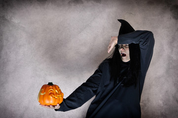 Witch holding Jack O'Lantern halloween pumpkin