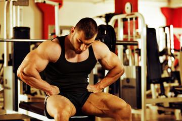 bodybuilder training gym, resting on the bench press