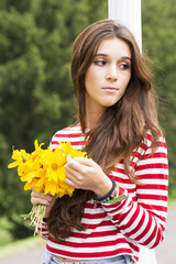 Romantic and pensive beautiful woman with flower bouquet.
