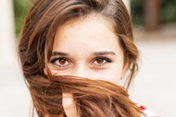 Closeup portrait of happy young woman covers her face of hair.
