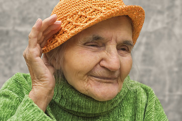 Elderly woman holding hand close to an ear.