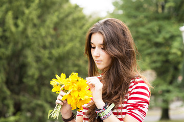 Beautiful romantic woman with flowers bouquet in the park.