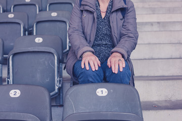 Elderly woman sitting on bleachers in empty stadium