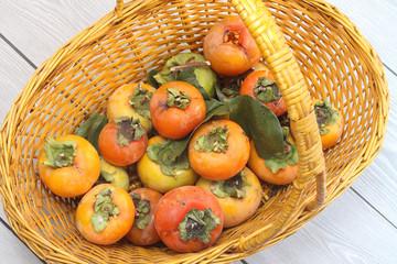 Kaki fruits in a wicker basket