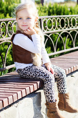 Little girl is sitting on the bench, autumn time