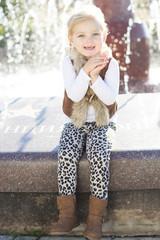 Little girl near fountain, autumn time
