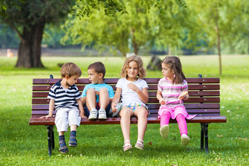 Cheerful Group of Children Sitting on Park Bench