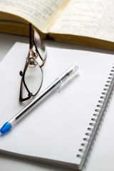 notebook with glasses and pen on table