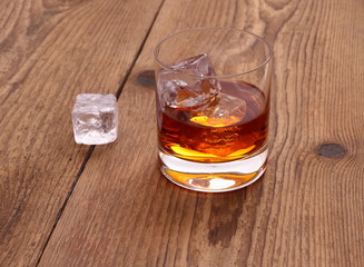 Whiskey with ice cubes in glass on wood background