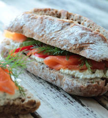 Sandwich with salmon, cream cheese and vegetables for breakfast
