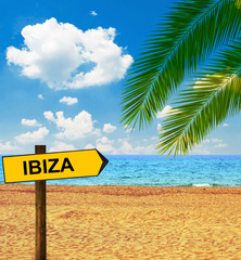 Tropical beach and direction board saying IBIZA
