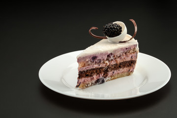 Cake triangular shape with black berries on a white plate